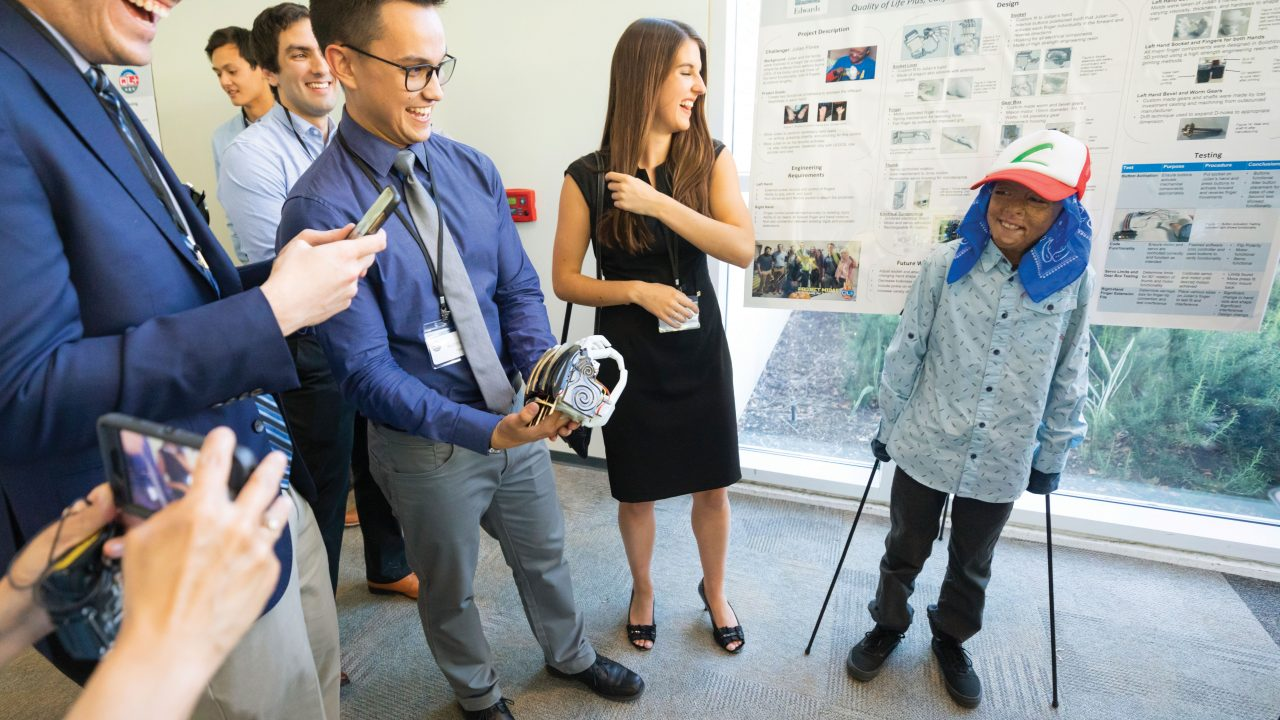 Ten-year-old car crash survivor Julian Reynoso stands with the help of crutches as a team of Cal Poly engineers presents him with a new robotic hand they designed in the Qualit of Life Plus lab on campus