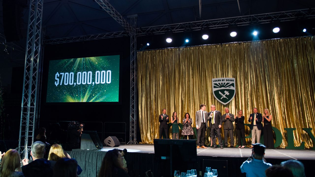 Cal Poly supporters, alumni and students join President Jeffrey Armstrong on stage of the Evening of Green and Gold event as he announces the Power of Doing's $700,000 million goal
