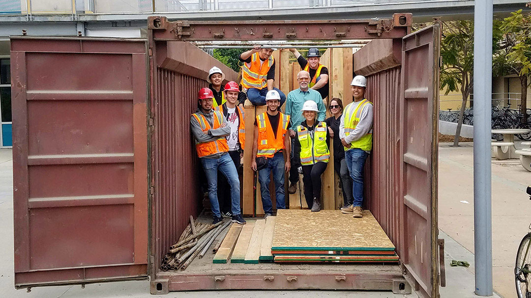 A team of Cal Poly architecture and construction management students stand in a mental container with the wooden frame components of new home bound for Weed, CA
