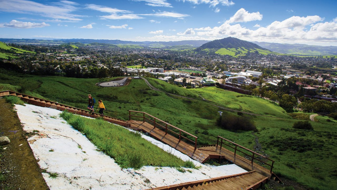 Two students hike alongside the Cal Poly P on the hill overlooking campus in spring 2019