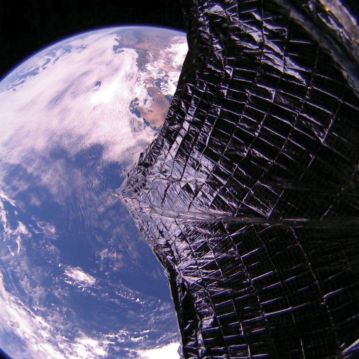 The unfurled metalic solar sail of the LightSail 2 appears before the earth in the background