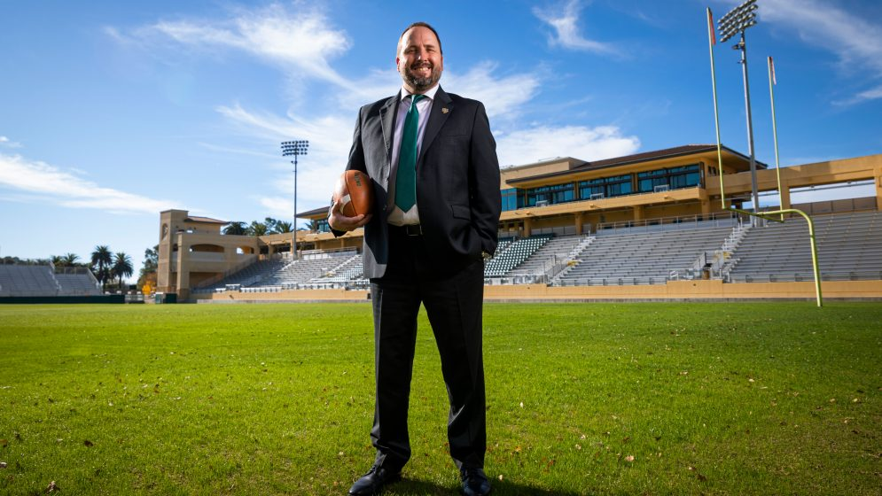 Football head coach Beau Baldwin holds a football in Spanos Stadium