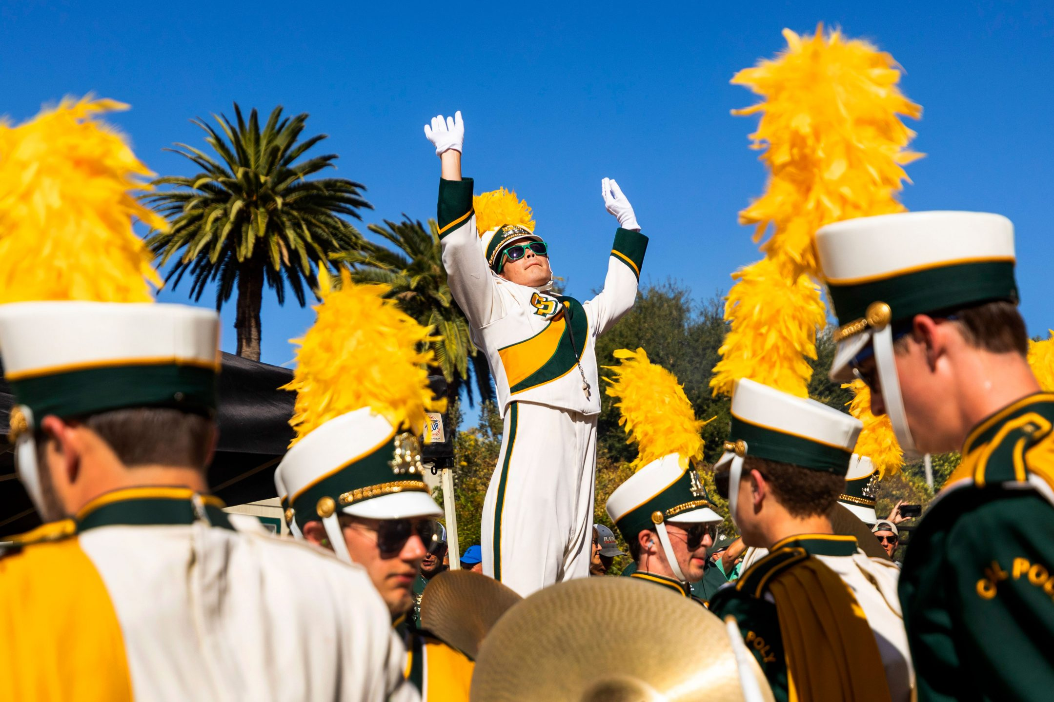 A Cal Poly drum major conducts the marching band at a football game tailgate
