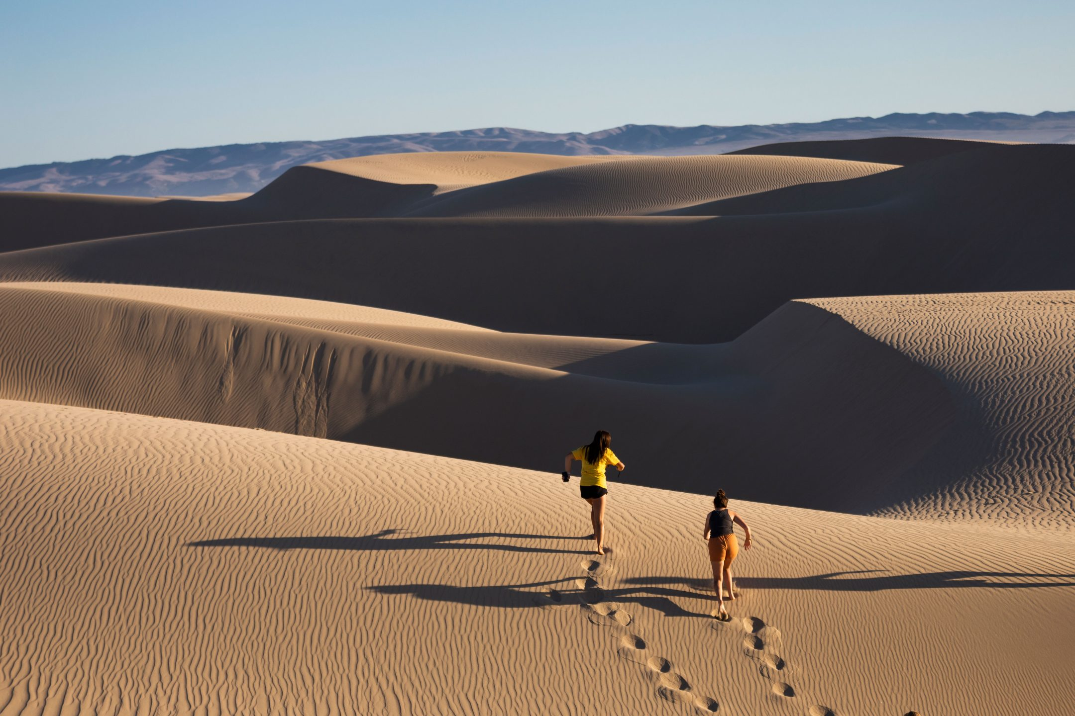 Students run along the Oceano Dunes during Week of Welcome