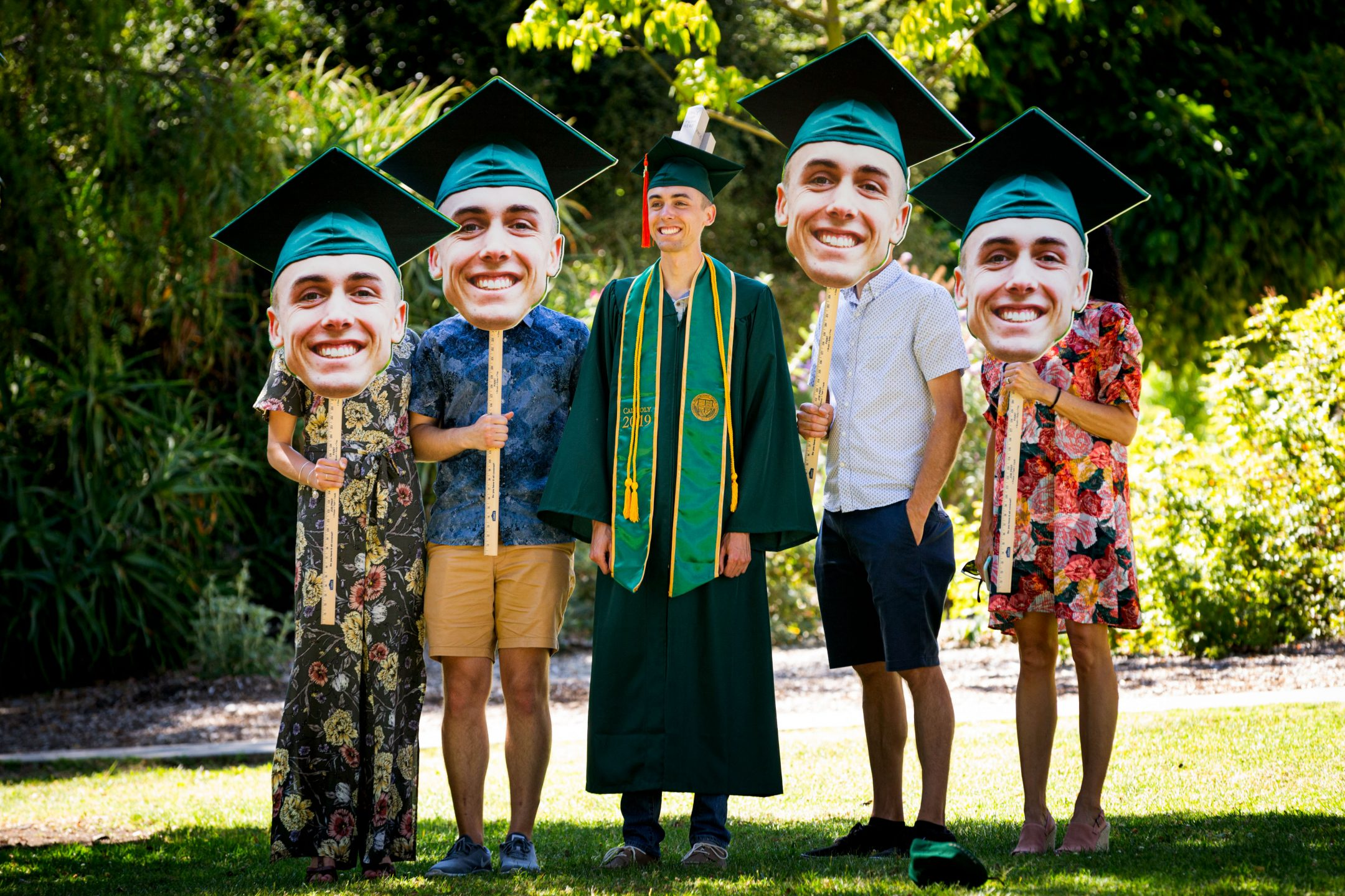 A Cal Poly graduate stands with his family hold photos of the graduates head at spring commencement