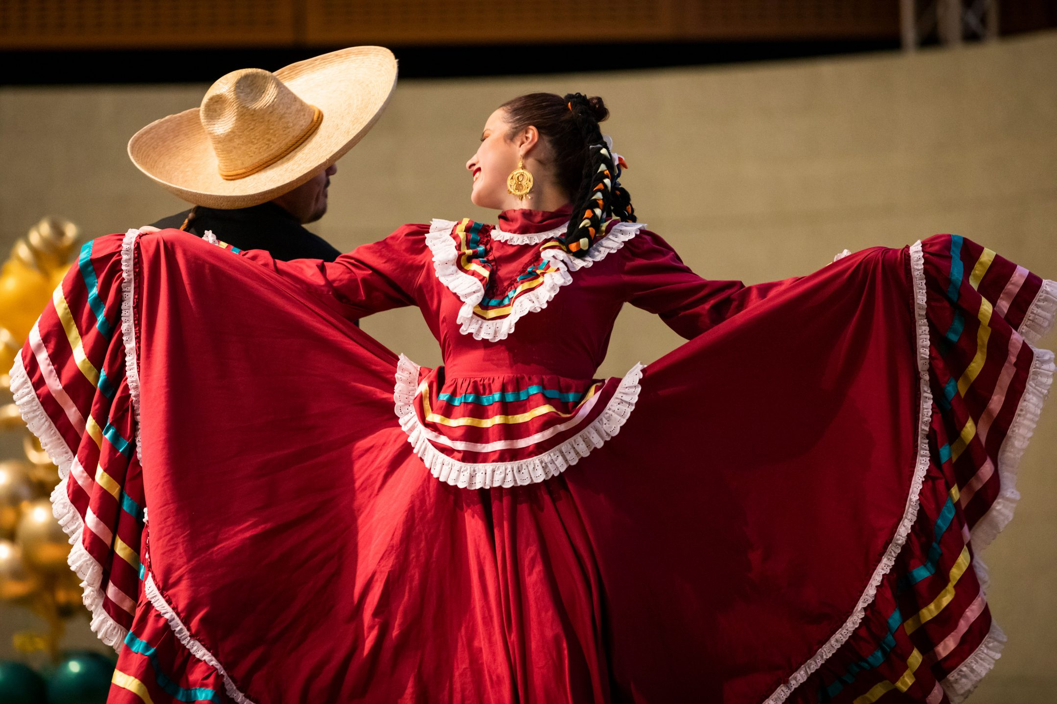 Dancers from Imagen y Espíritu Ballet Folklórico de Cal Poly perform on stage in traditional Mexican dress