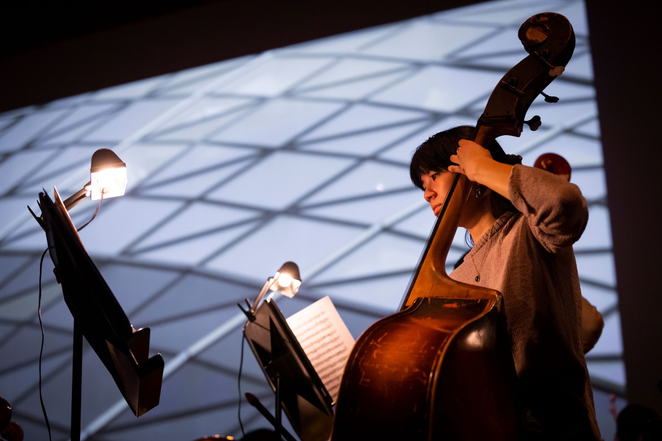 A student playing the upright bass rehearses at the Performing Arts Center at Cal Poly in front of a large-screen projection