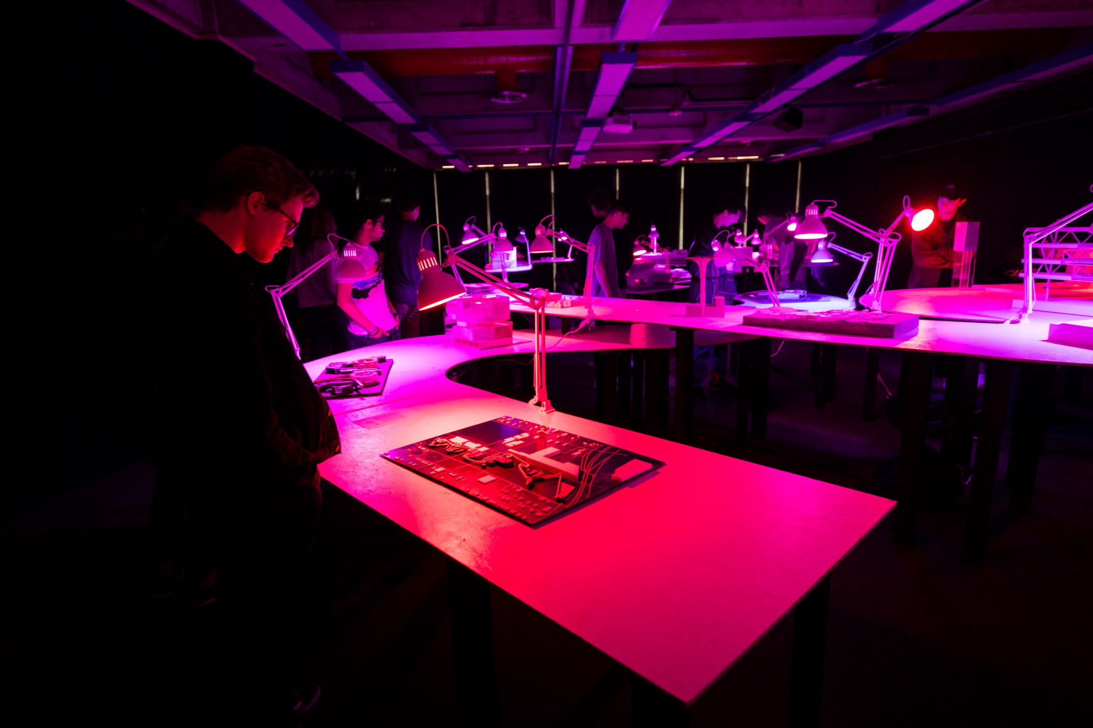 """Students observe architecture student models lit with pink and red lights at the senior showcase, """"Yours Truly."""""""