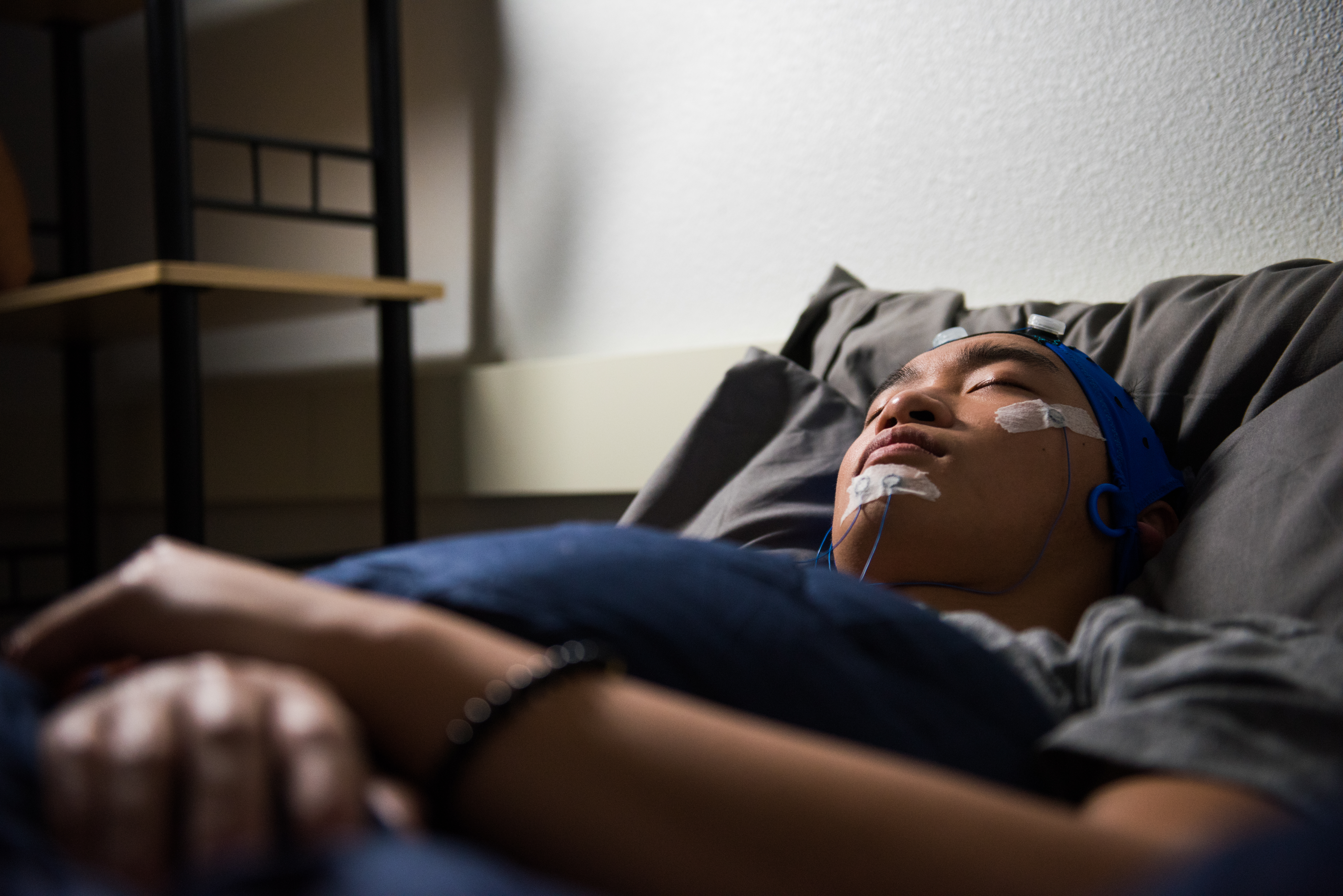 A young man sleeps on a bed in a dimly-lit room, his face connected to several monitoring wires.