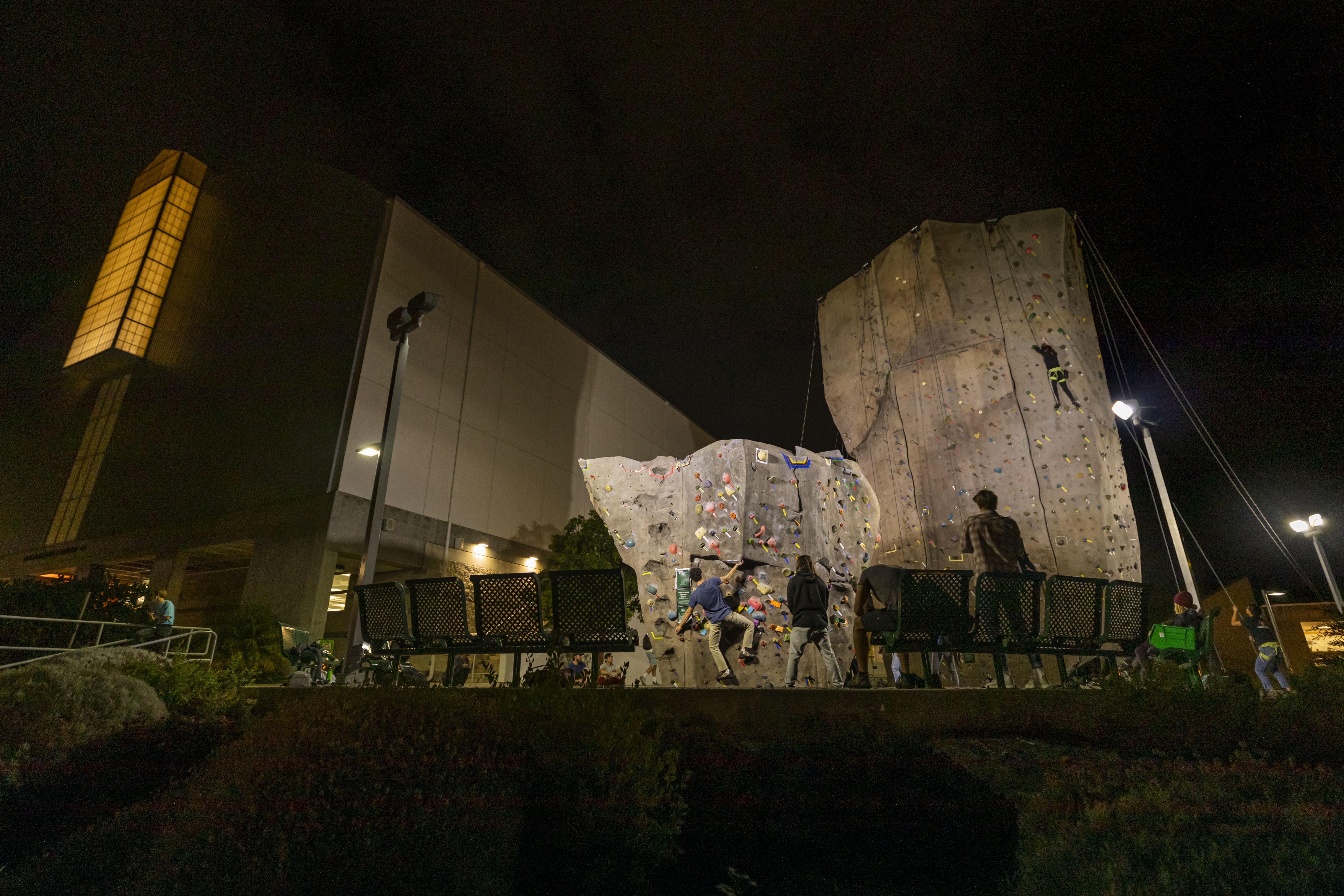 Students climb on the university's rock climbing park at night.