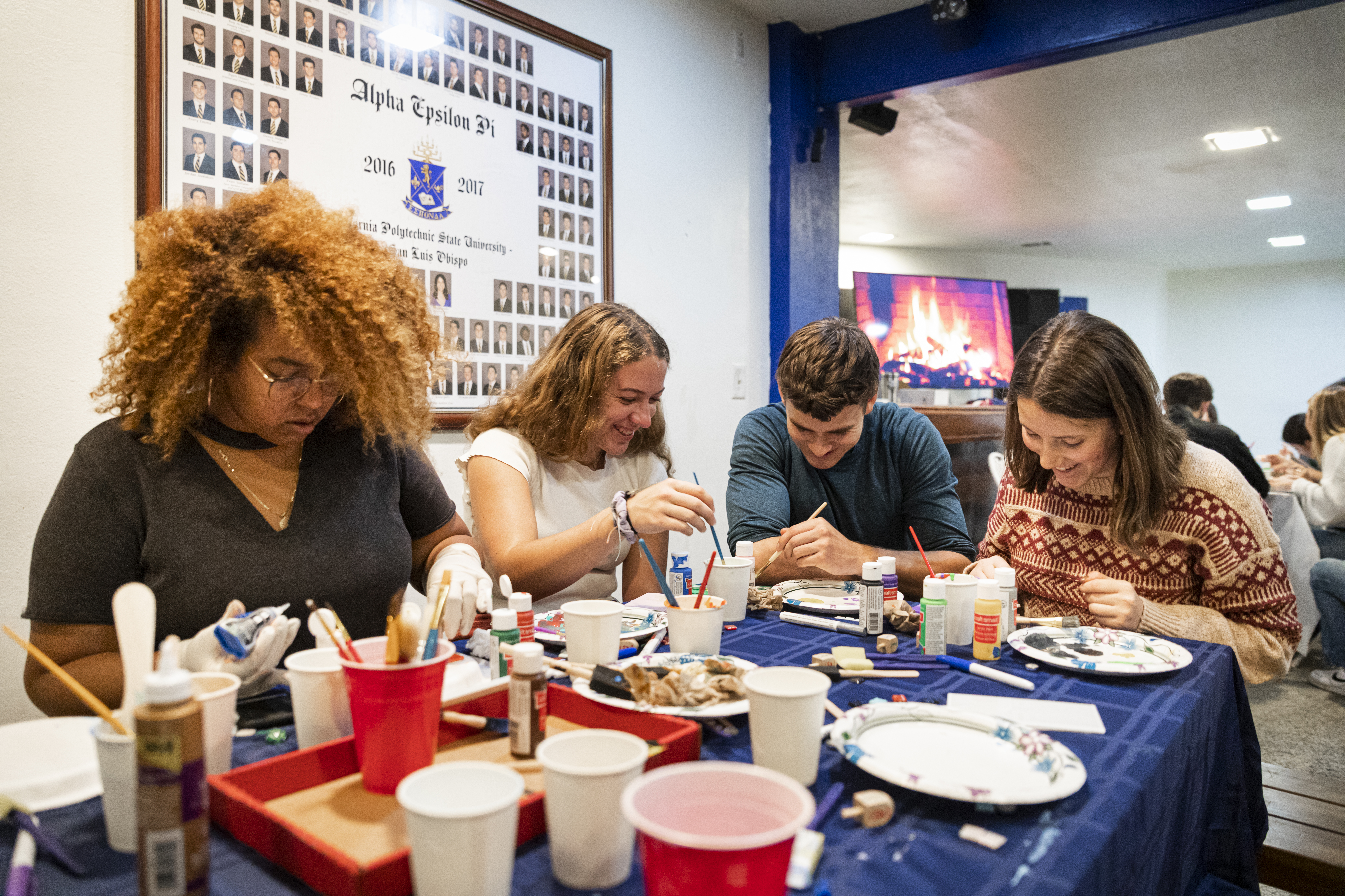 A group of students sit around a table piled with crafting supplies, with a display of fraternity members on the wall behind them and a virtual fireplace burning in the background.