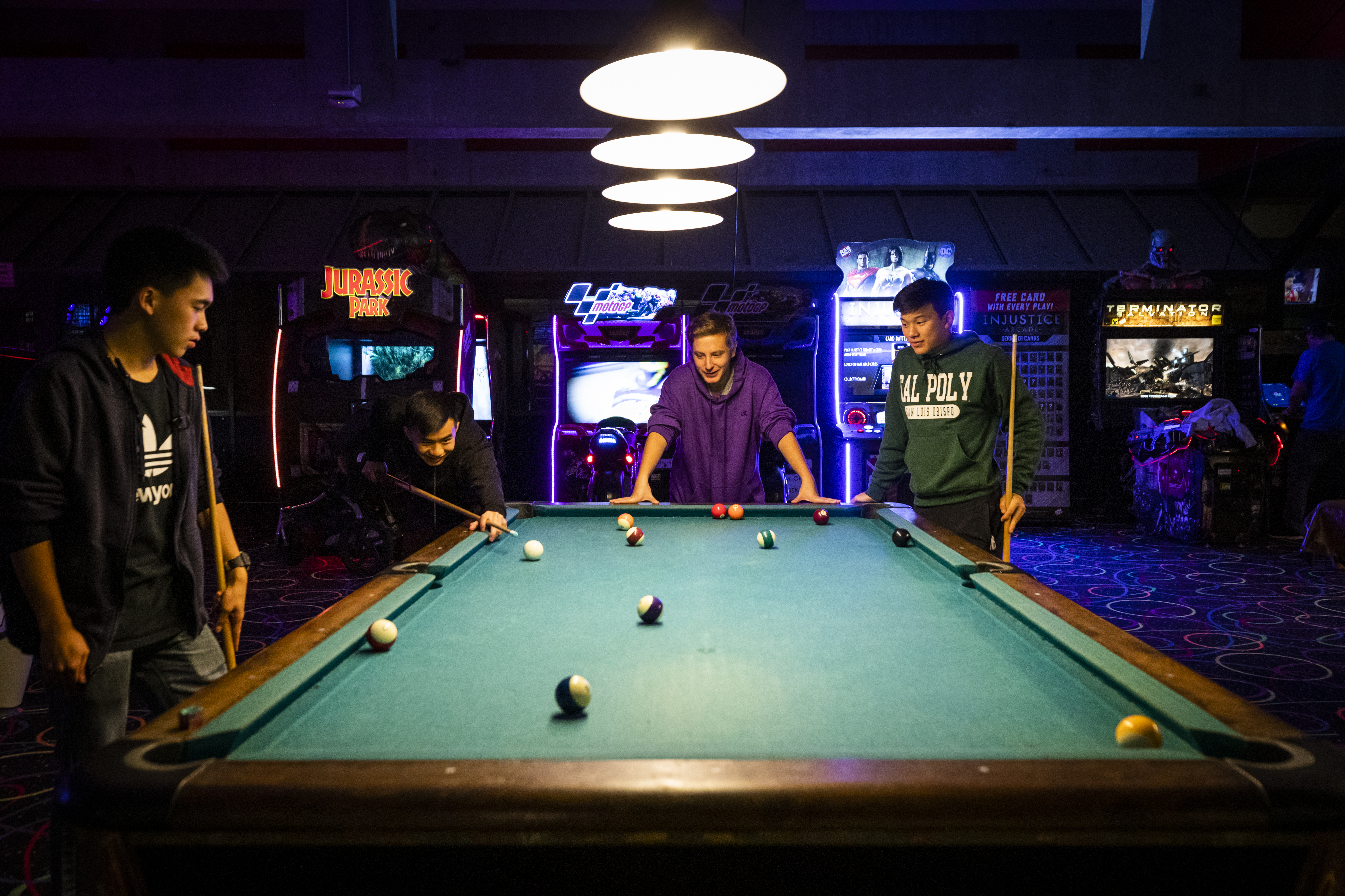 Four young men stand around a pool table in a dark arcade, lit from lamps above and video game cabinets in the backgroun.