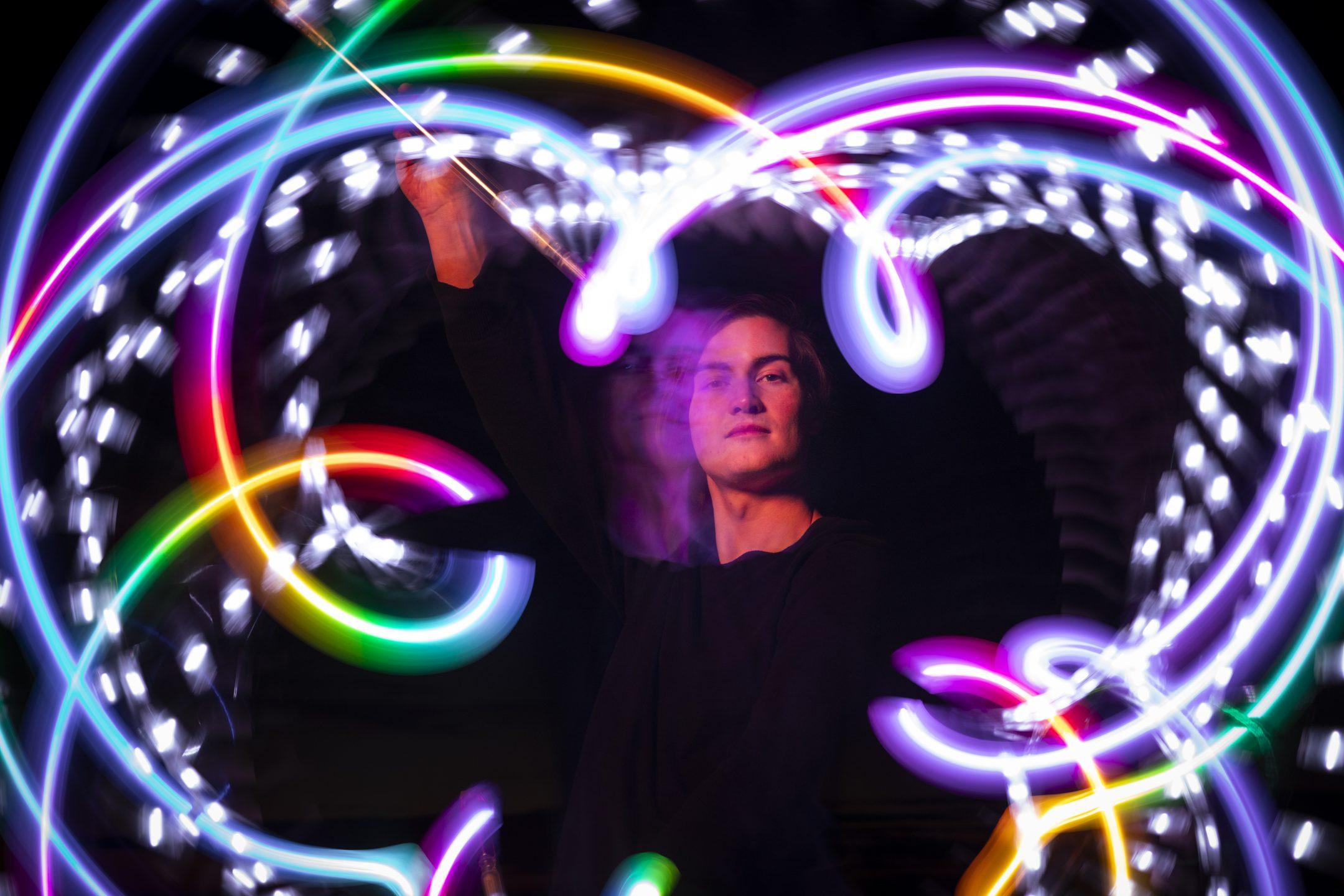 A glow artist wearing black swirls multicolored lights in a pattern