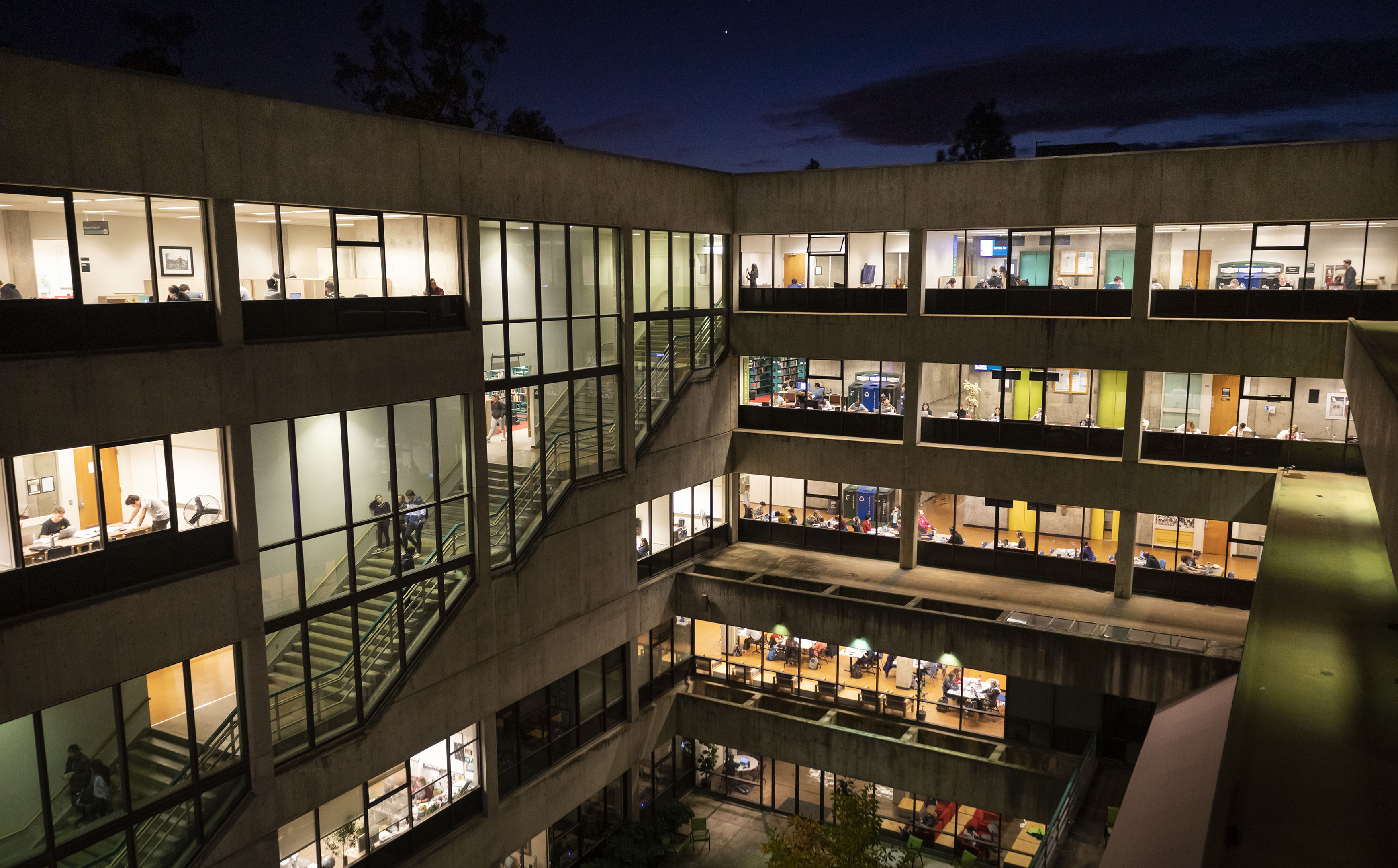 The atrium of Cal Poly's Kennedy Library lit and filled with students studying