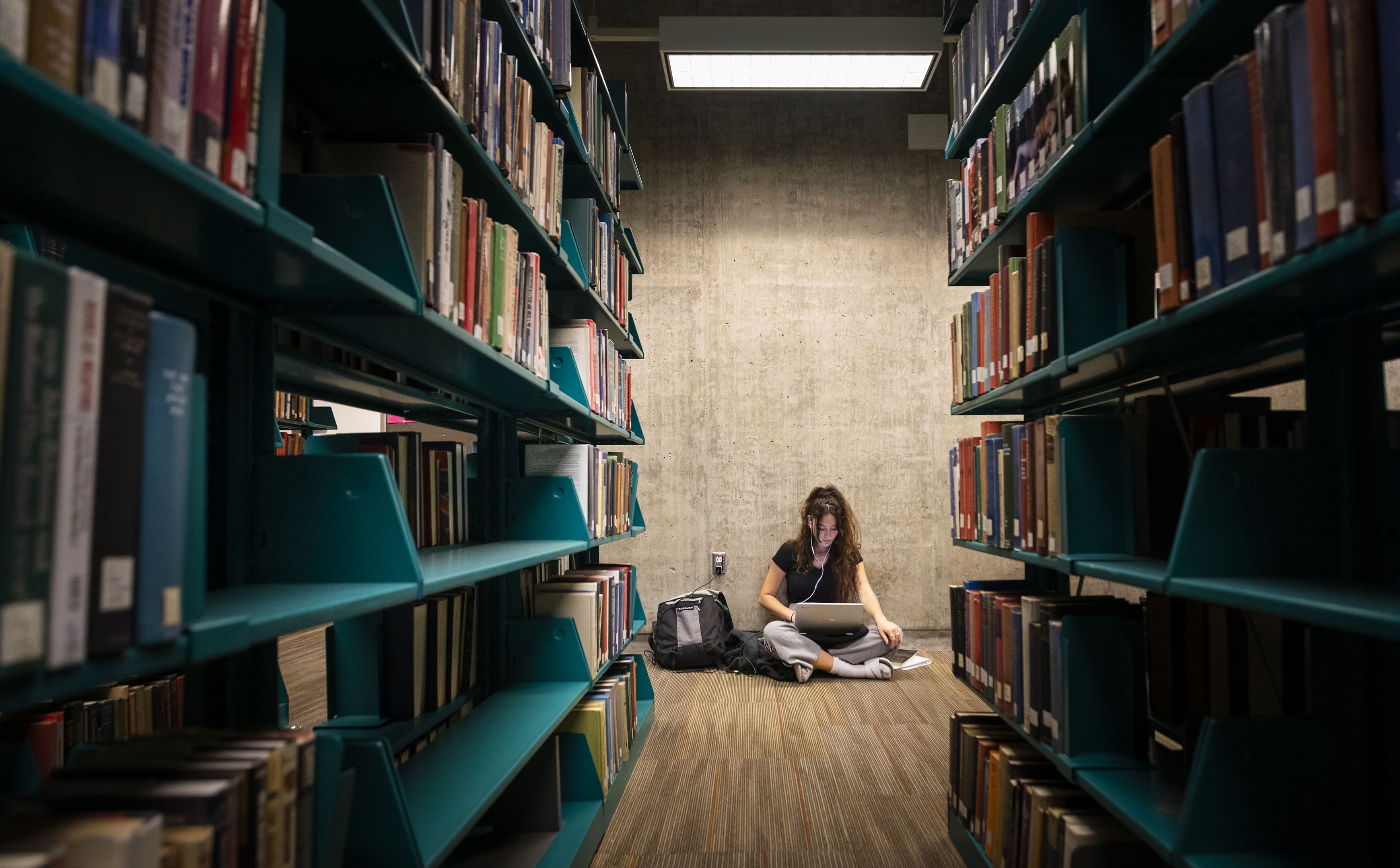 A woman sits on the floor with a laptop and backpack between rows of bookshelves in Cal Poly's Kennedy Library
