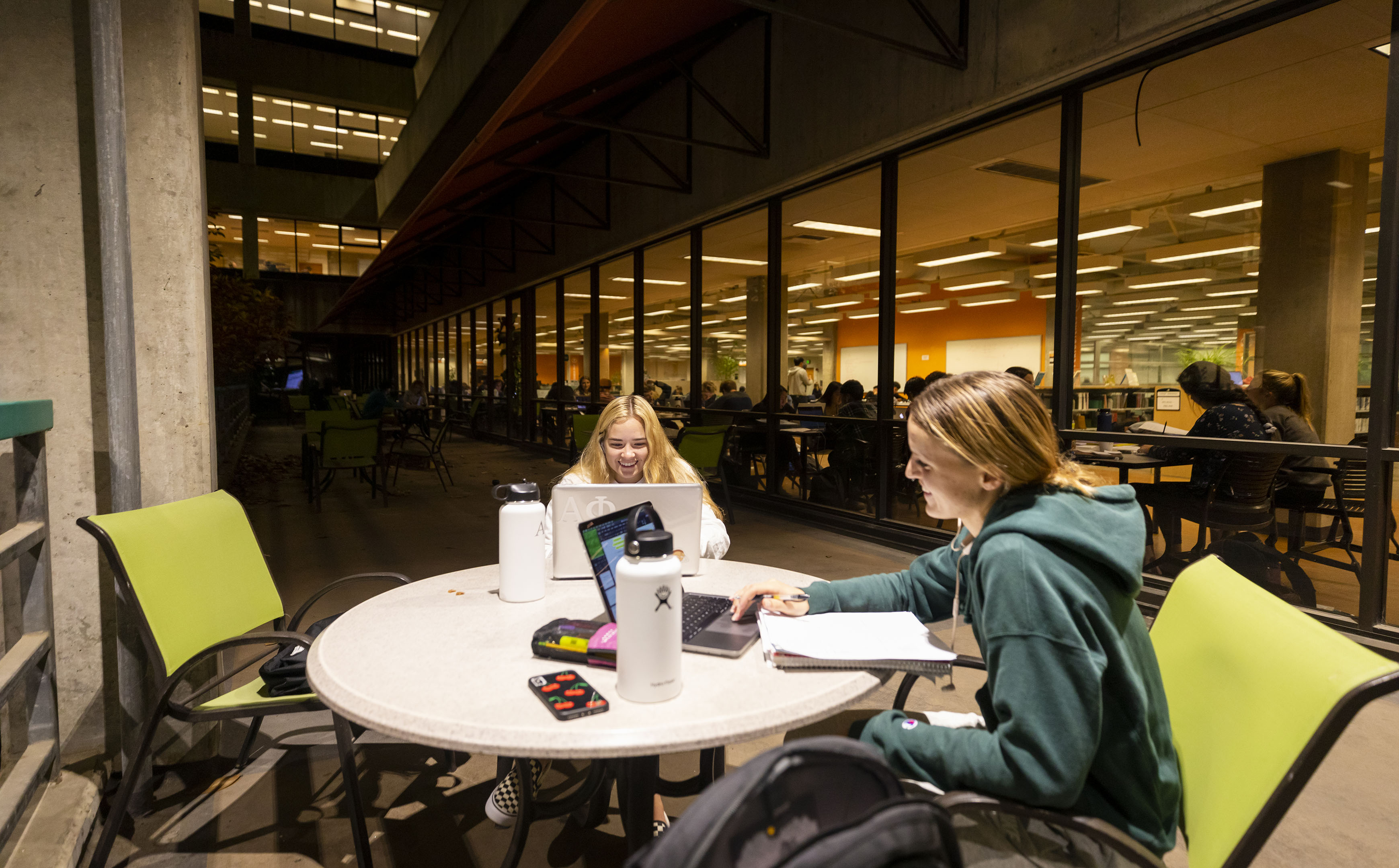 Two female students sit at a table with notes, waterbottles and laptops in Kennedy Library's atrium