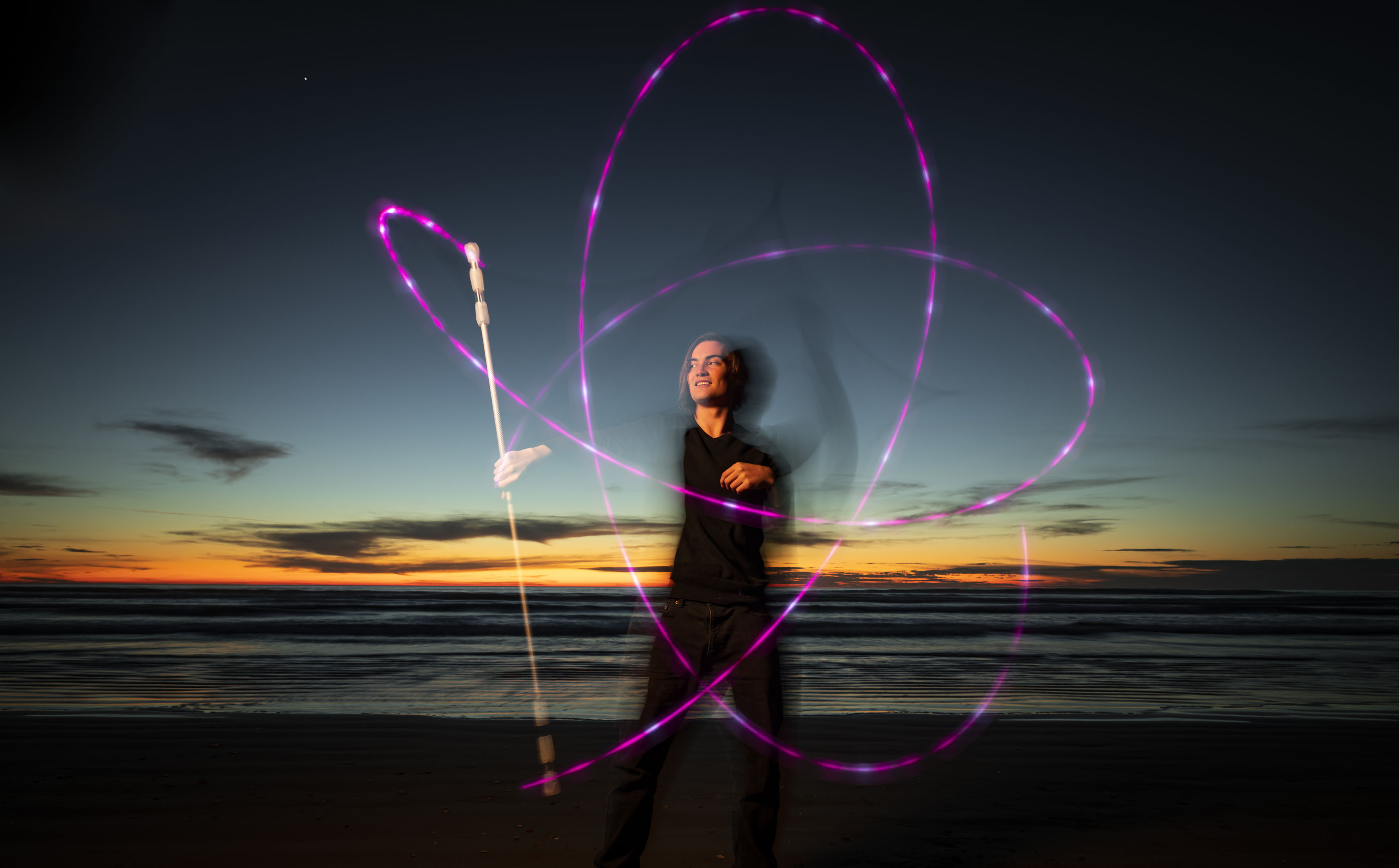 A young man stands on the beach tracing a pattern with a purple light on a long stick as the sun sets in the background