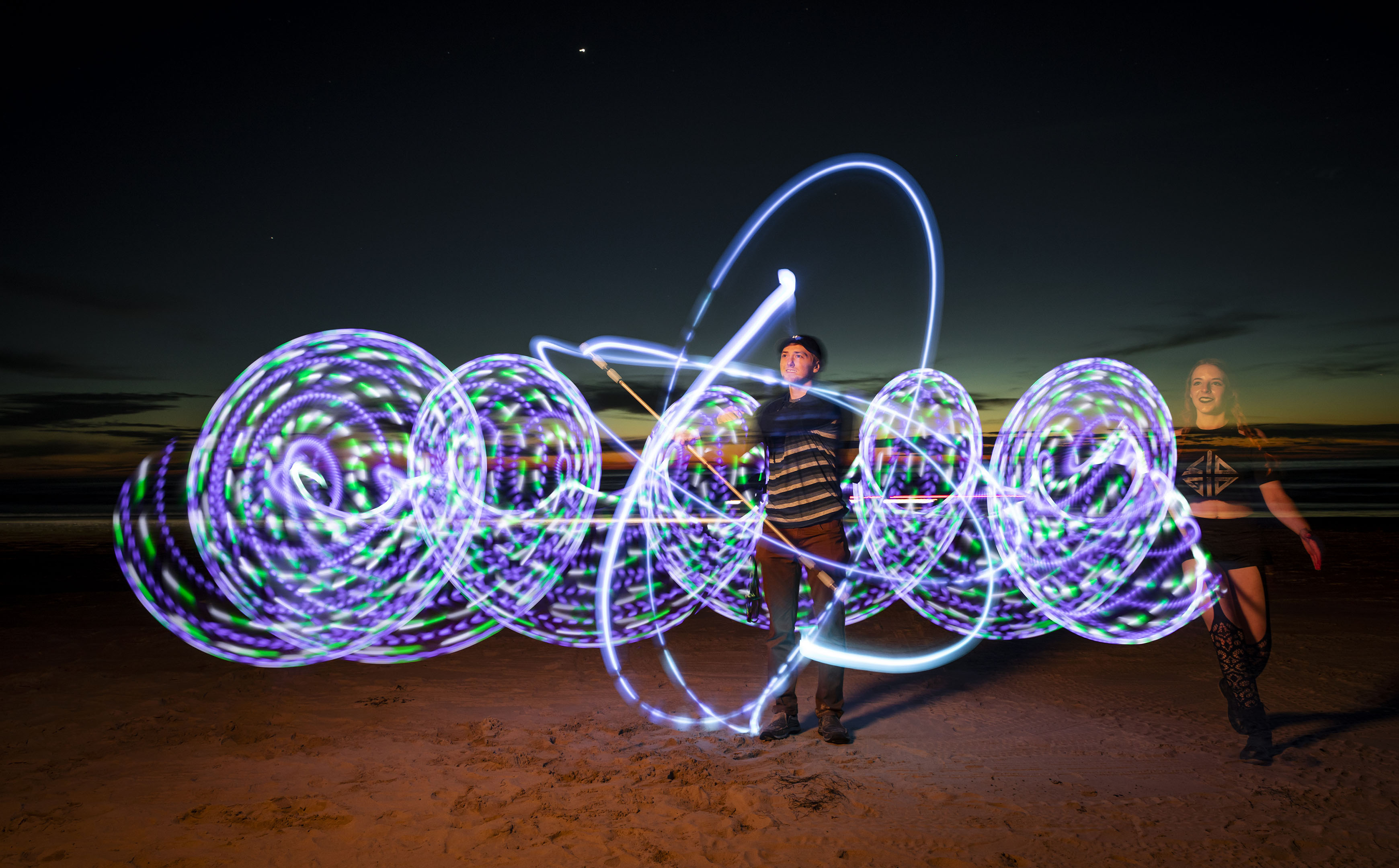 A young woman and man stand on the beach swirling lights to create a purple and green pattern