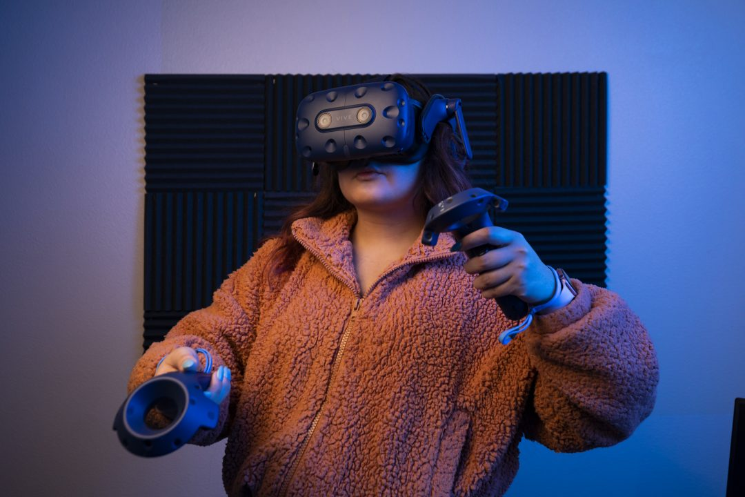 A young woman in an orange sweater and a VR visor handles a set of VR controls.
