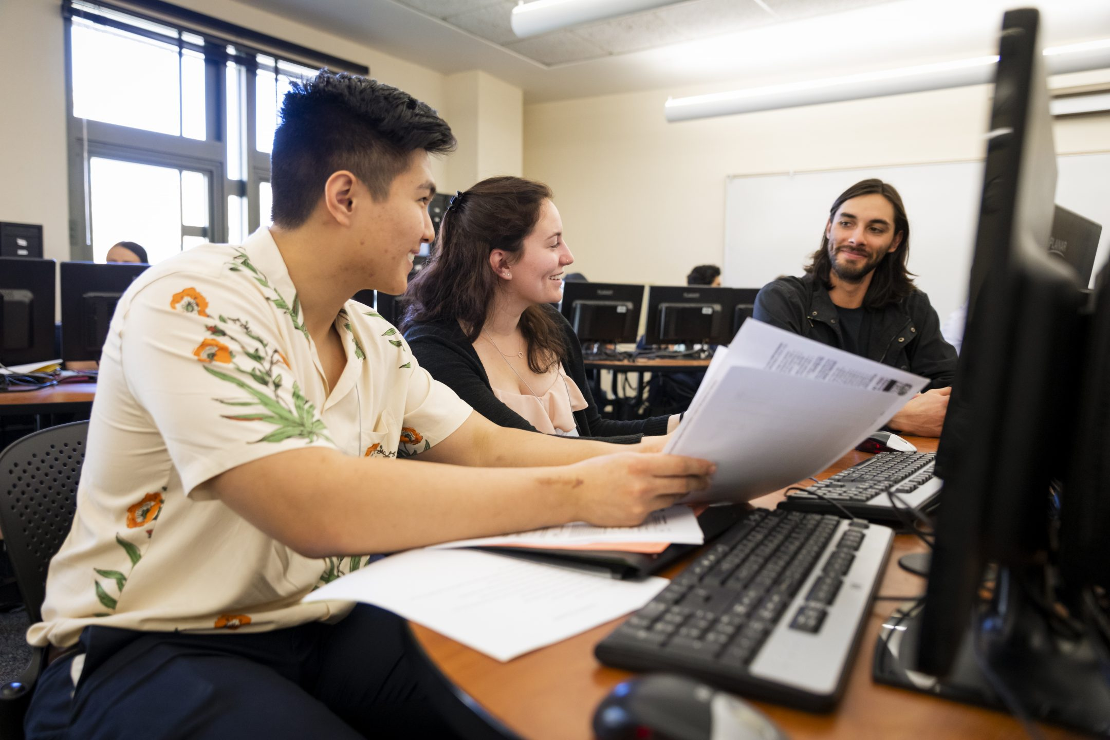 Two students sit at a desk reviewing tax forms with a young man.