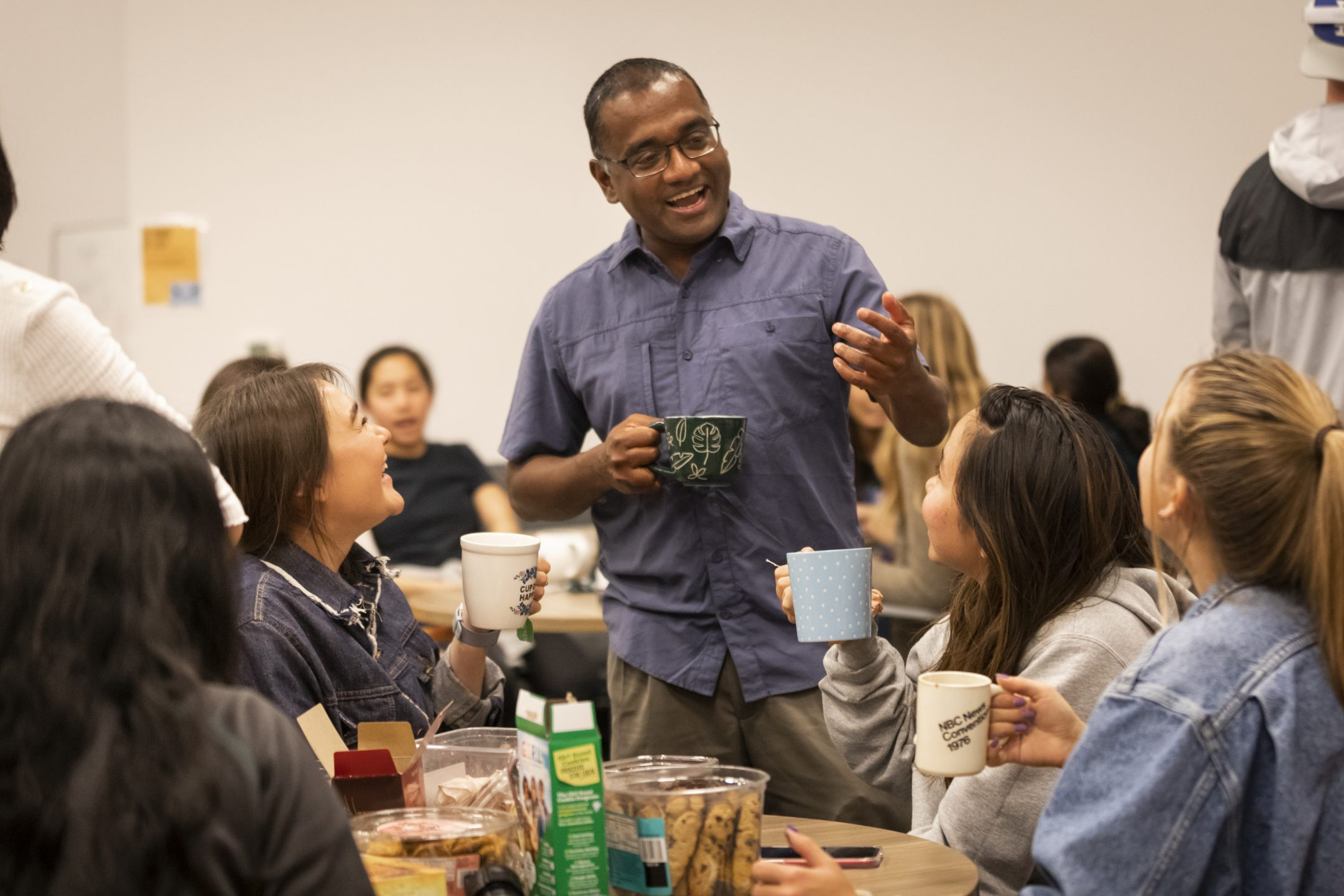 A professor in a blue shirt stands with a tea cup, chatting with students sitting at a table.