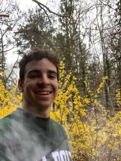 A young man in a Cal Poly t-shirt hikes among trees and yellow flowers.