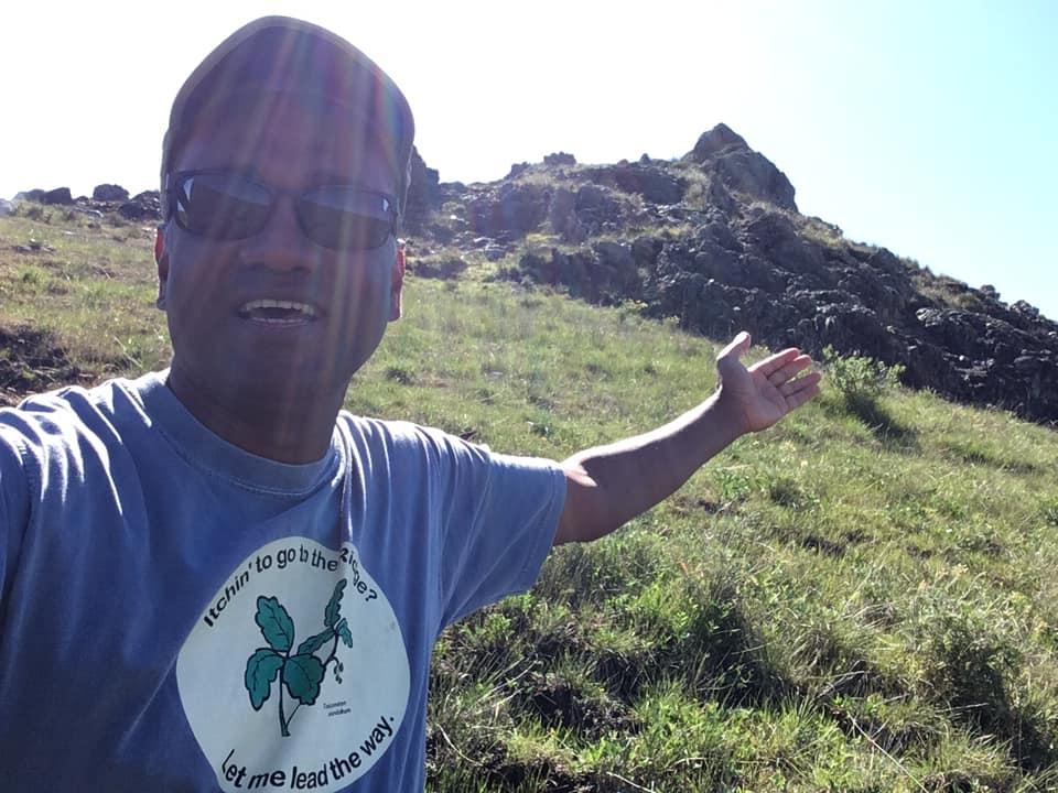 Rajakaruna, in a baseball cap and sunglasses, in a selfie taken on a sunlit hillside