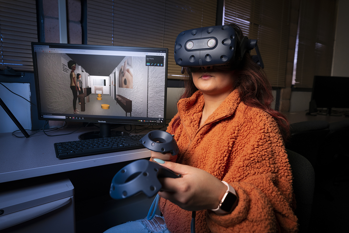 A young woman in an orange sweater pilots a VR experience, in front of a monitor showing a digital rendering of a massage parlor.