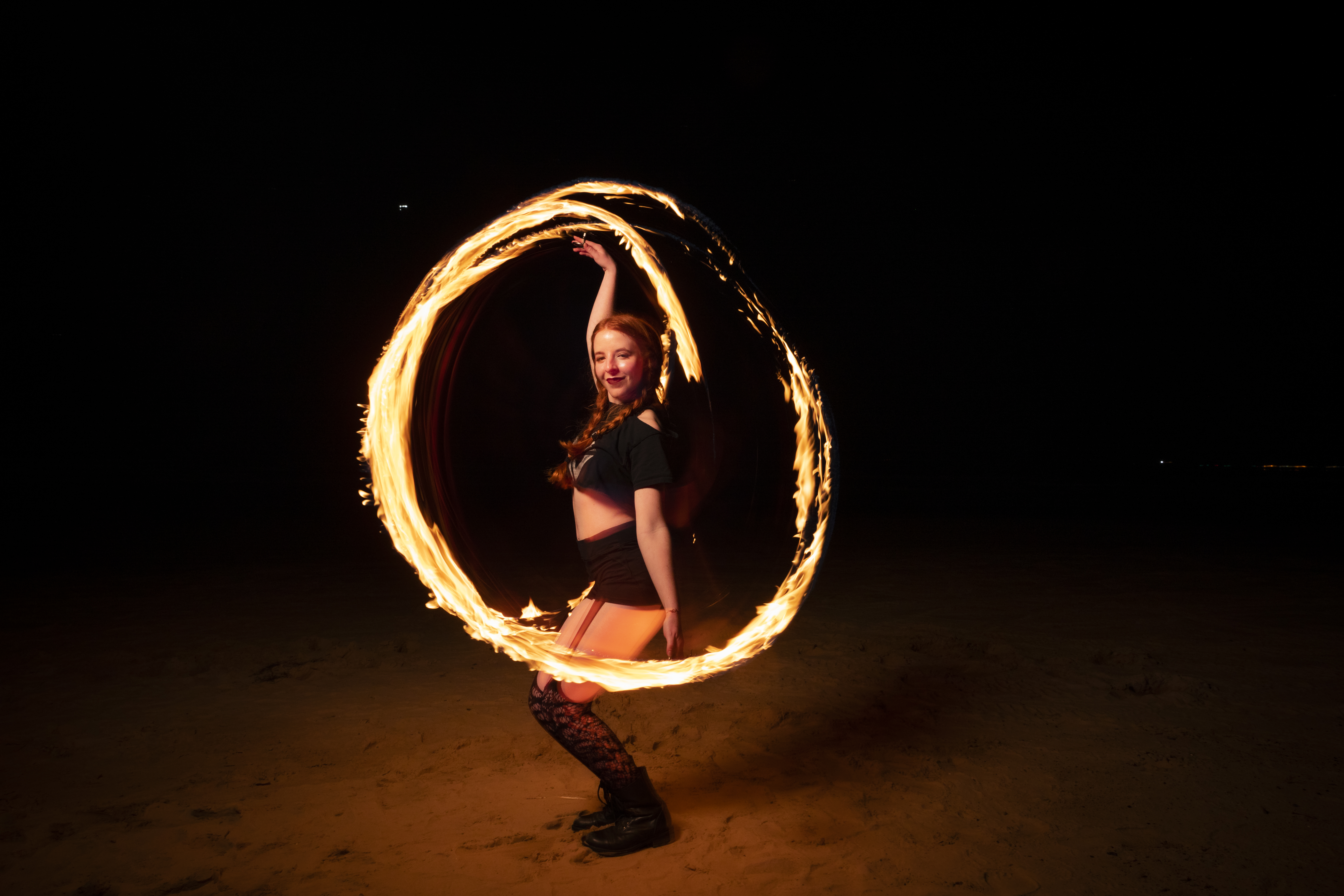 A young woman stands on the sand illuminated by an apparent ring of fire.
