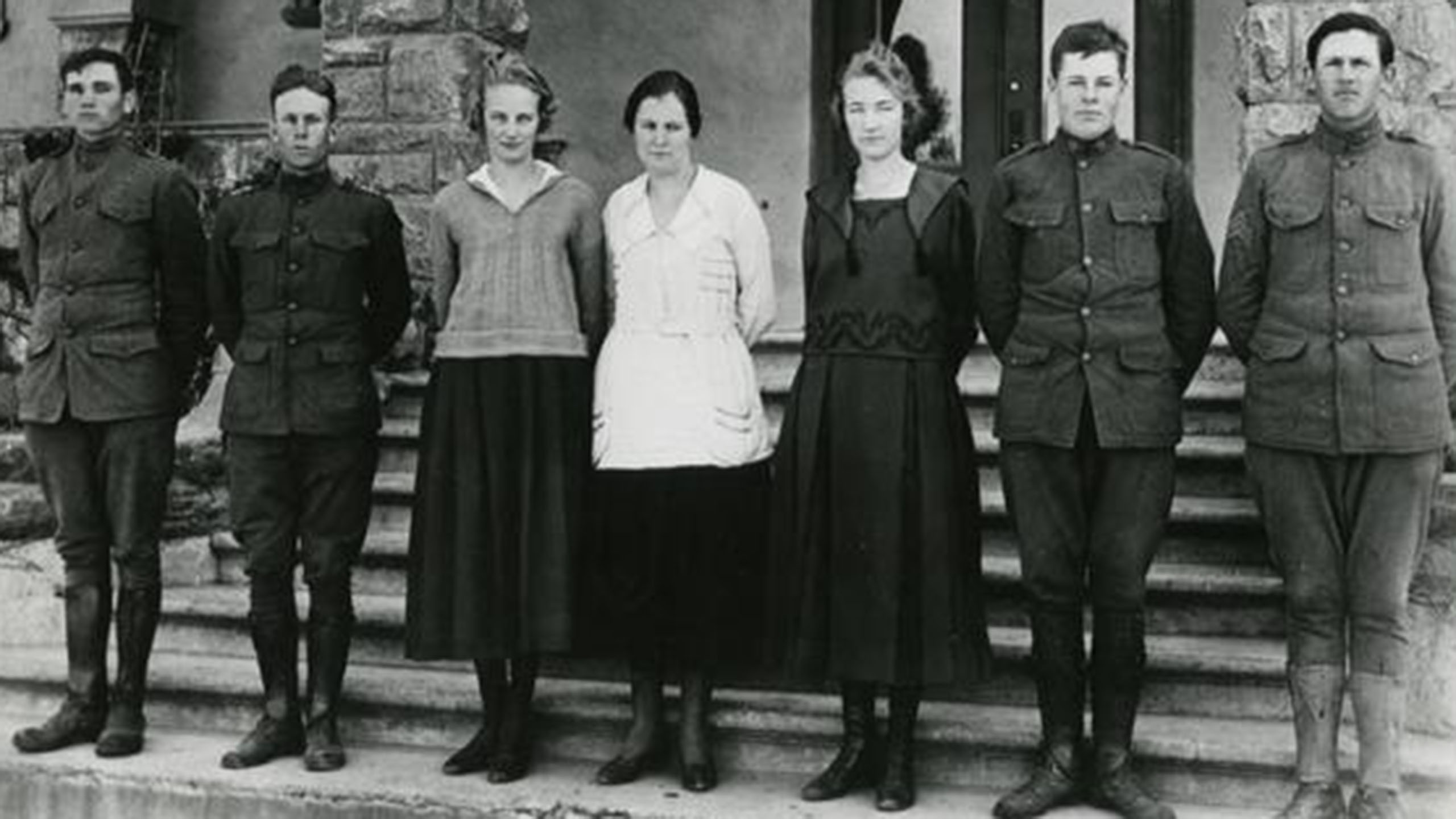 Seven students, men in early 20th-century military uniforms and women in long blouses and skirts, pose in front of a campus building in a vintage photo