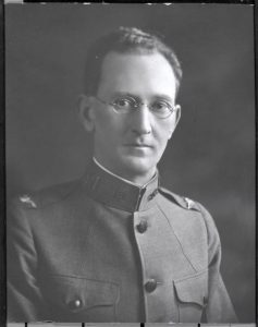 A man in glasses and a military uniform poses for a black and white bust portrait