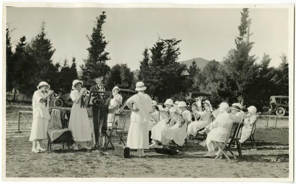 A group of musicians, women in long white dresses and hats, perform instrumental music on a campus lawn in a black and white photo.