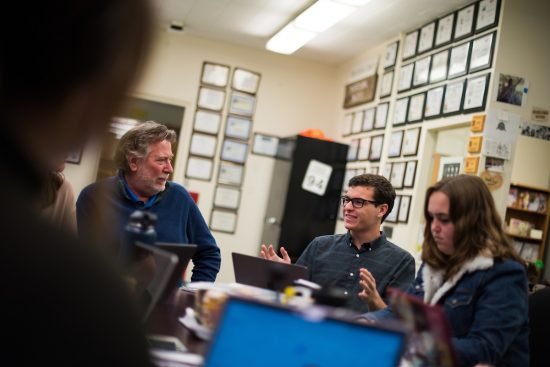 A young man sits at a table, in discussion with a professor and several fellow students in the offices of Mustang News.