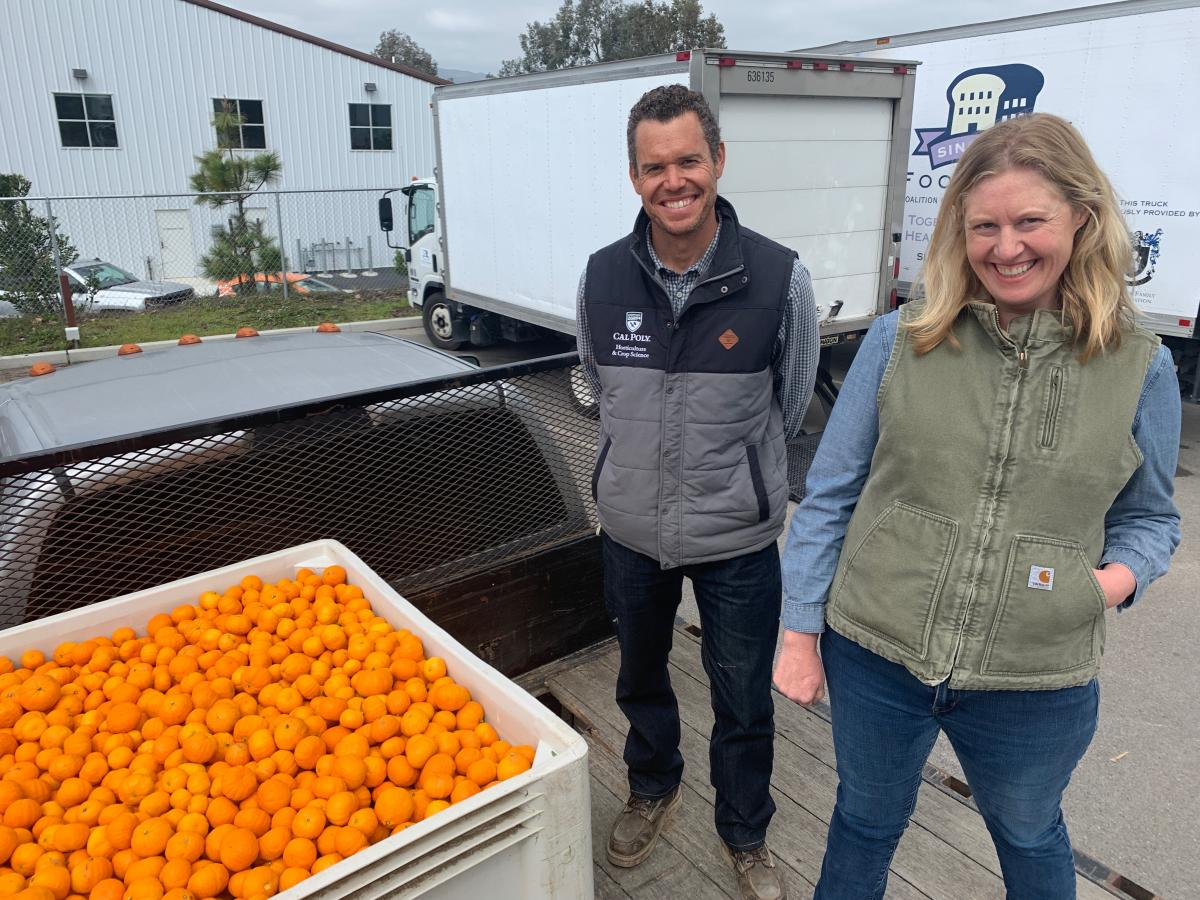 "A man and a woman stand in the bed of a truck next to an enormous crate of mandarin oranges, in front of a panel truck painted with ""Food Bank of SLO"""