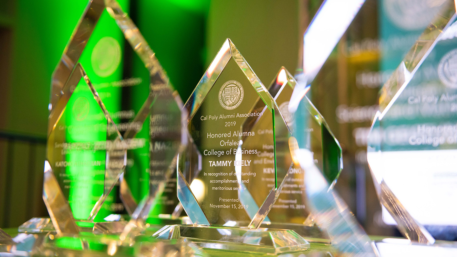 A group of clear glass awards on a table, backlit with green and white light