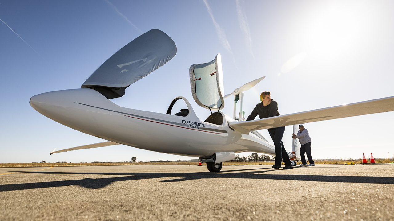 Professor Paulo Iscold pushes a lightweight experimental aircraft onto a tarmac for a test flight.