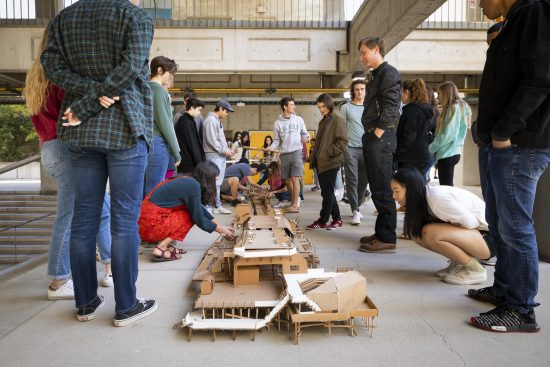 Students gather around wood architectural models displayed on the concrete courtyard of the Architecture building.
