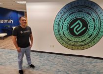 Manvir Sandhu stands in the entryway of the Zennify offices
