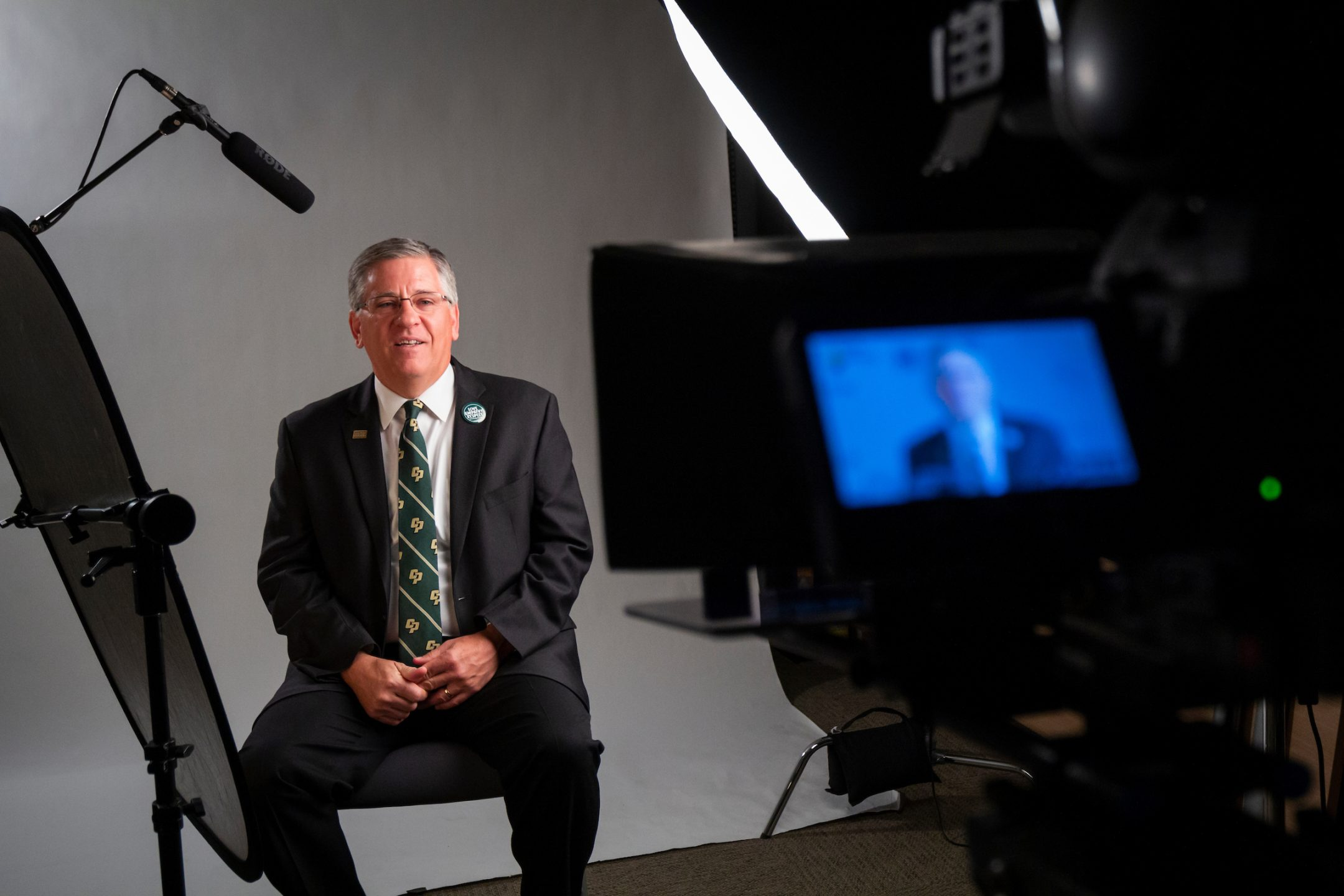 President Armstrong, in a suit and Cal Poly tie, speaks into a video camera and microphone in front of a white backdrop