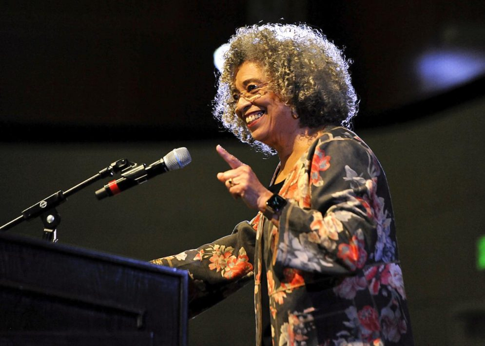 Angela Davis gestures while speaking into a microphone at a Cal Poly event.