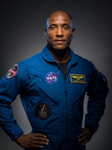 Dramatic portrait of Victor Glover, in a blue flight suit with NASA and Navy insignia