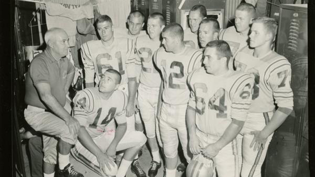 A black and white photo of a football coach and 10 uniformed players in a locker room