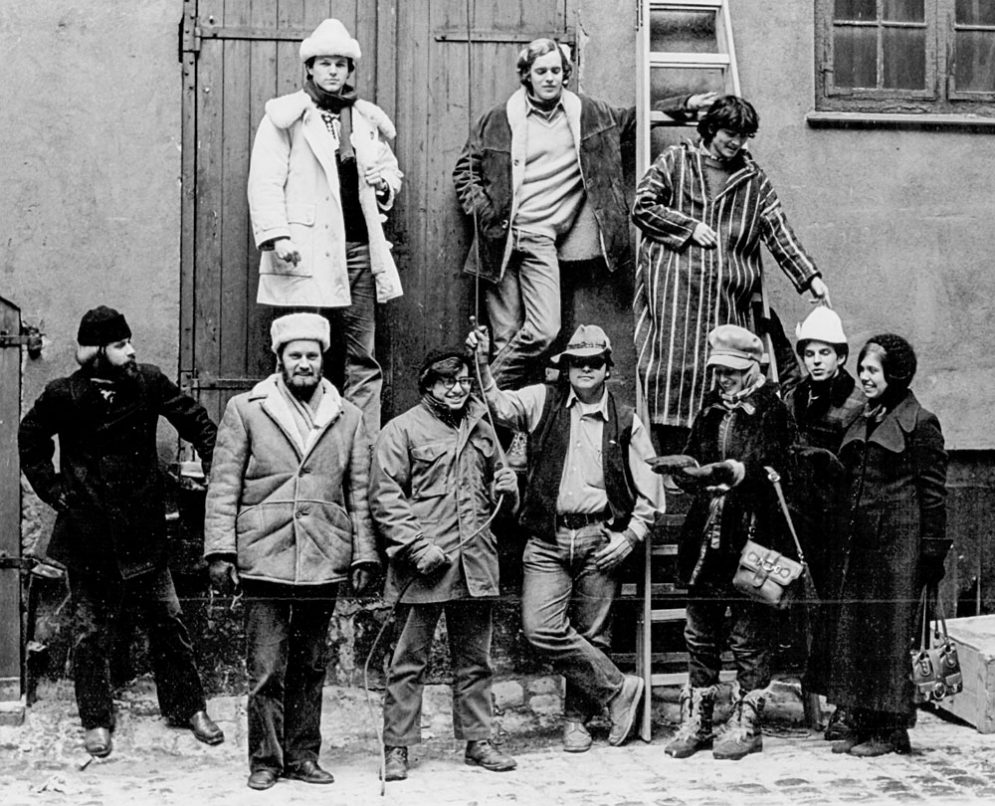 A black and white image of group of ten people standing in winter coats