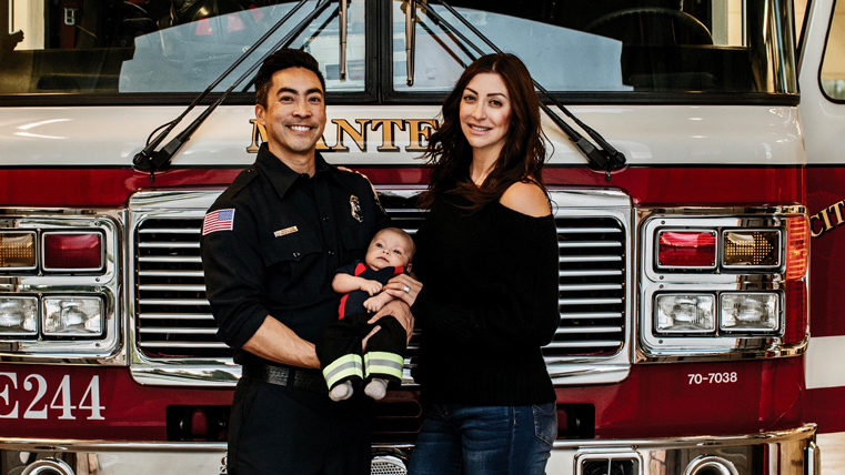 A man in a fire fighter's uniform holds his son with his wife in front of a fire engine