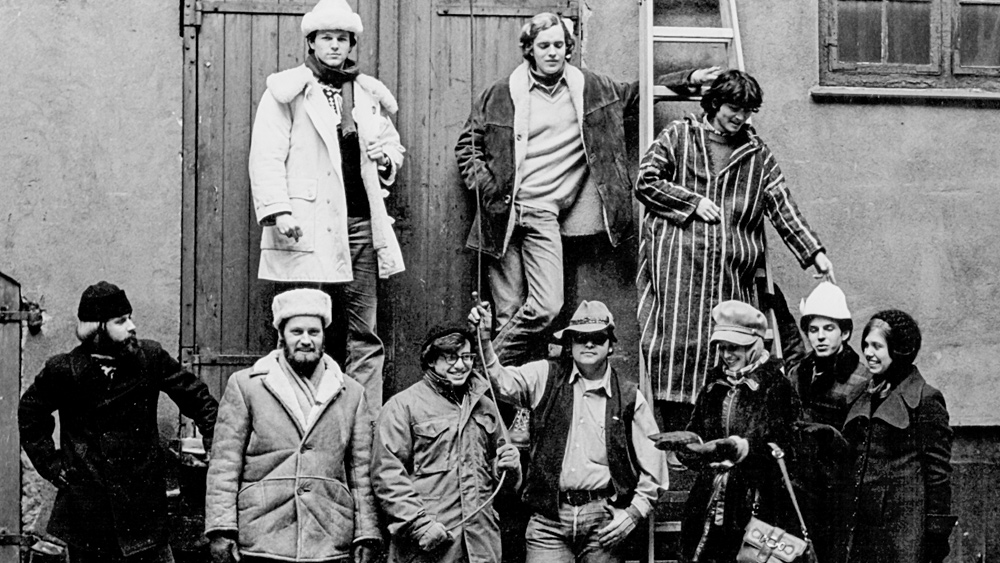 Ten people in winter coats stand together in a black and white image