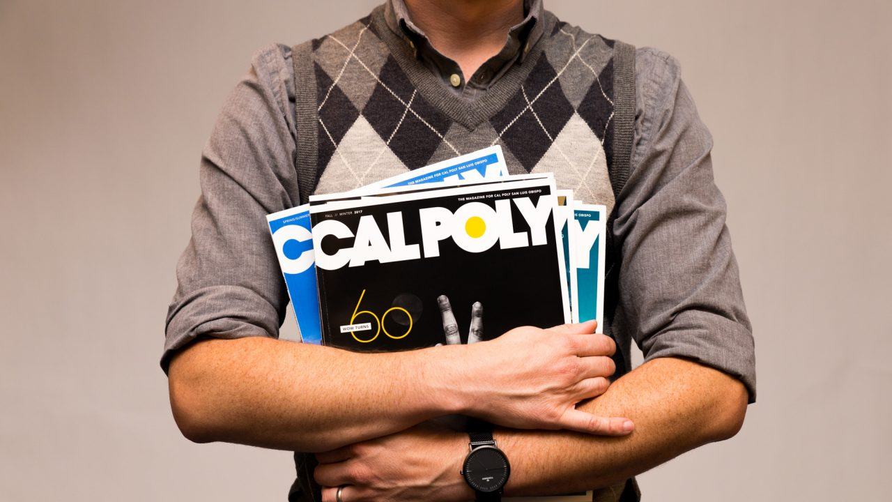 A man in a grey shirt holds a stack of Cal Poly Magazine copies
