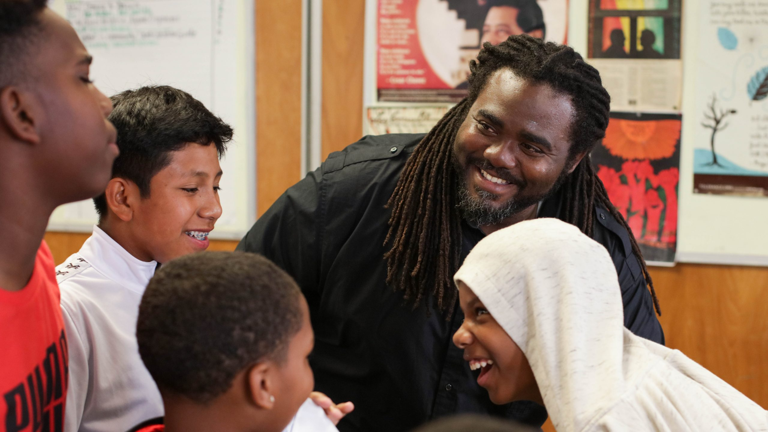 A man smiles at a group of laughing middle school boys
