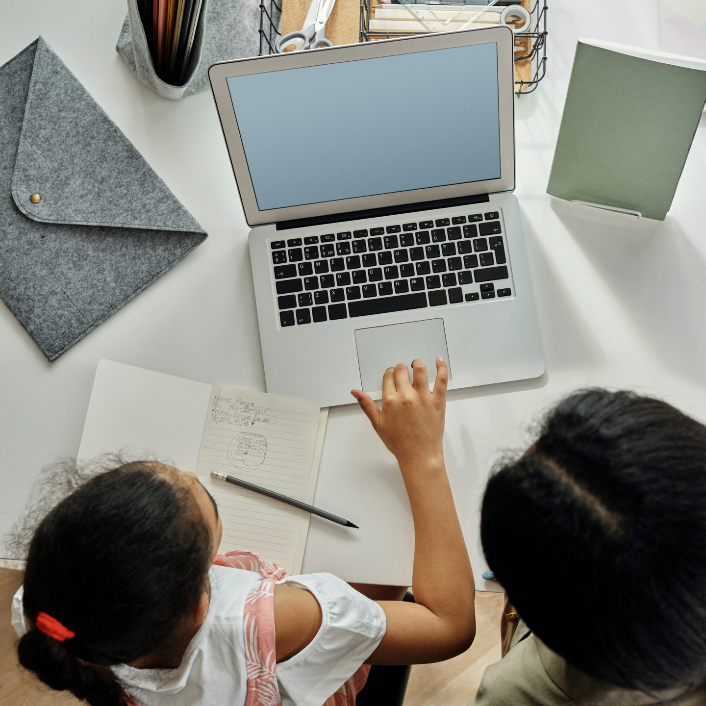 A child and a woman sit in front of a laptop on a white desk