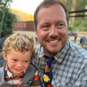 A man in a plaid shirt holds his son