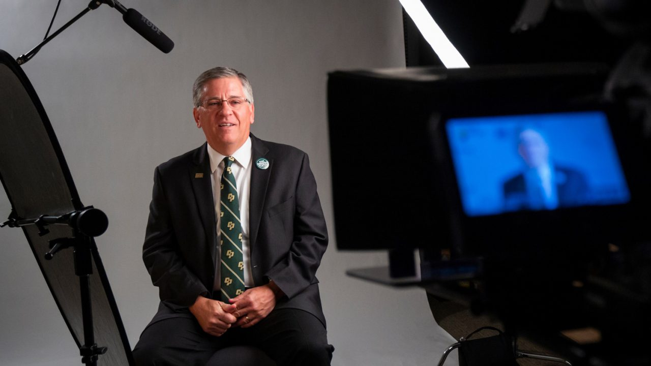 President Jeffrey D. Armstrong sits in front of a white backdrop on a video set